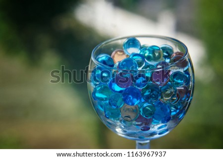Transparent glass with gel balls on a dark green background. An unusual drink.                                #1163967937
