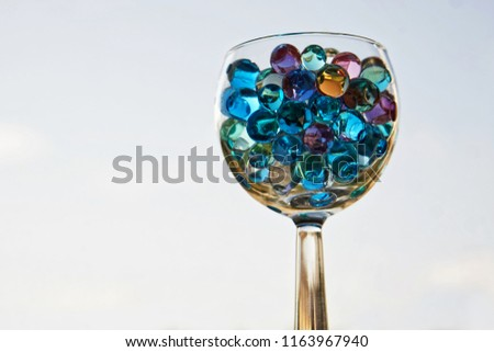 Transparent glass with gel balls on a light background. An unusual drink.                                #1163967940