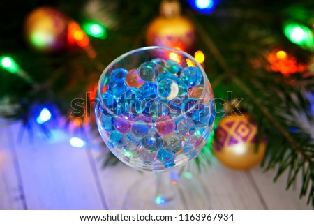 Transparent glass with gel balls on the background of a Christmas tree. An unusual drink.                                #1163967934