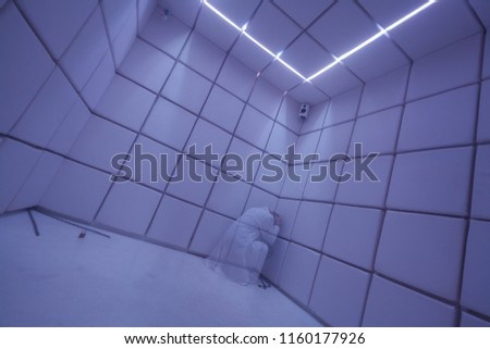 Transparent isolated ghost-like patient person wearing white smock holding head with hands in the corner of an asylum pedlam madhouse psychiatric clinic ward hospital room.  Stock photo ©