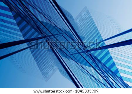 Transparent modern architecture. Tilt double exposure photo of high-rise office building reflecting in glass wall of another office building. Abstract composition with geometric structure.