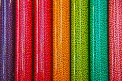 Transparent plastic tubes full of thousands of colorful candies