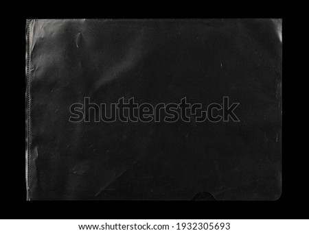 Transparent plastic wrap on the black background. Clean blank texture overlay effect template. Isolated wrinkle surface branding mock-up. Black pack packaging bag.