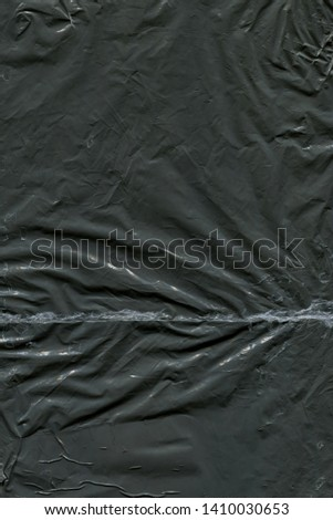 Transparent plastic wrap on the black background. Plastic bag texture. Reusable trash and waste.