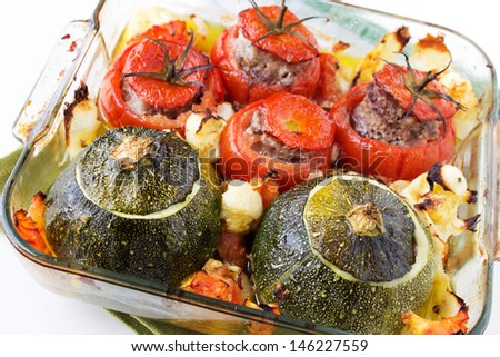 Transparent plate with cooked tomatoes and marrows stuffed with minced meat with sauce.