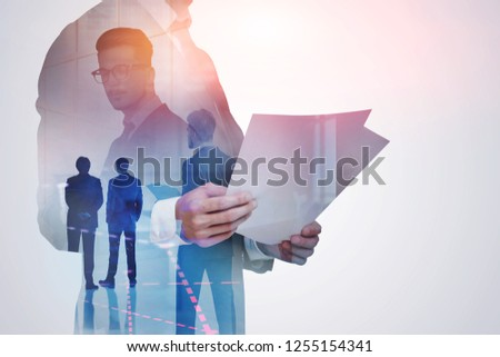 Transparent portrait of unrecognizable businessman looking at documents with double exposure of his colleagues and graph in the foreground. Toned image #1255154341