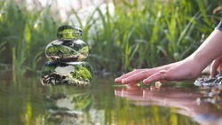 Transparent stones in water Zen pyramid. Stones of the volume inside the stones nature, flowers. Children's or woman's hand above the water surface. Concept - peace of mind, inner peace, harmony