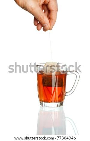 Transparent teacup and hand holding tea bag