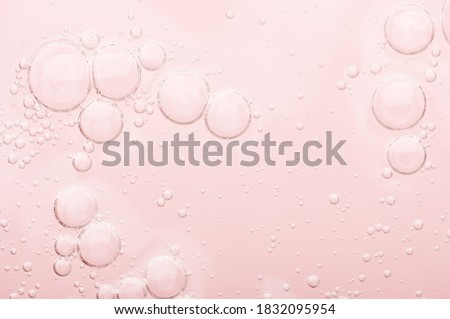 Transparent texture of moisturizing serum on a pink background. Gel water lotion for skincare. Cosmetic liquid beauty product with retinol and vitamins for face and body skin care.