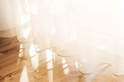 Transparent white curtain tulle from an open window. Sunny day, the sun's rays sunlight penetrate the room.