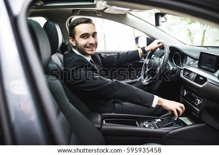 transport, business trip, destination and people concept - close up of young man in suit driving car look at camera