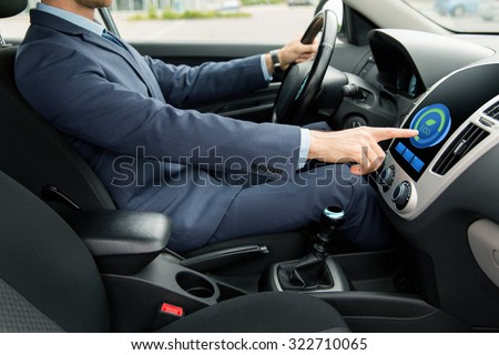 transport, business trip, technology and people concept - close up of young man in suit driving car and adjusting car eco mode system settings on dashboard computer screen #322710065