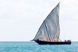 transport dhow as seen from a distance showing flapping sails against an open ocean and flat horizon before setting sail