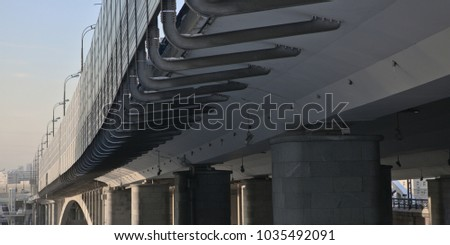 Transport Industrial Bridge From Below On Sunset Background. Bottom And Side View Of Reinforced Concrete Bridge.