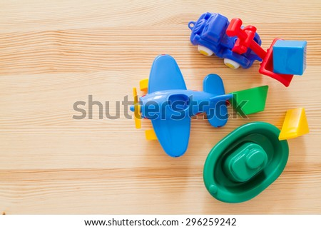 Transport infrastructure concept - toy ship, truck and plane, wood background, top view