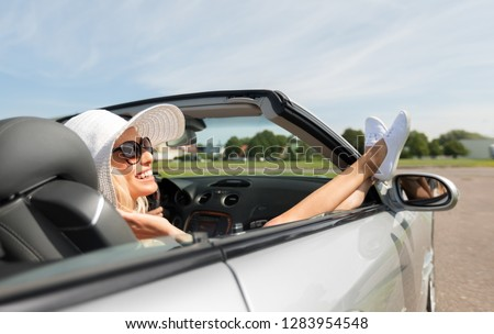 transport, leisure and people concept - happy woman in summer hat and sunglasses chilling in cabriolet car outdoors