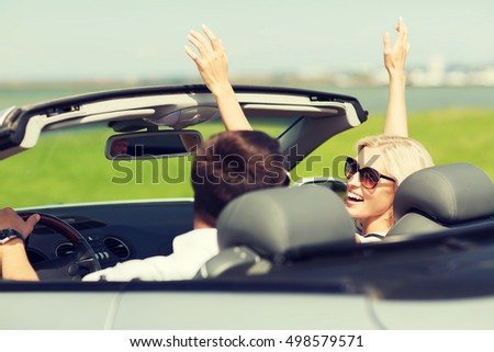 transport, road trip, leisure, couple and people concept - happy man and woman driving in cabriolet car outdoors #498579571