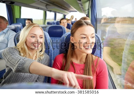 transport, tourism, friendship, road trip and people concept - young women or teenage friends riding in travel bus #381585016