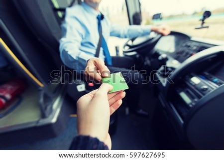 transport, tourism, road trip and people concept - close up of bus driver taking ticket or plastic card from passenger