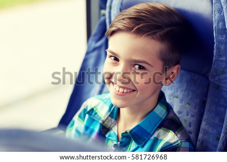 transport, tourism, road trip and people concept - happy boy sitting in travel bus or train #581726968