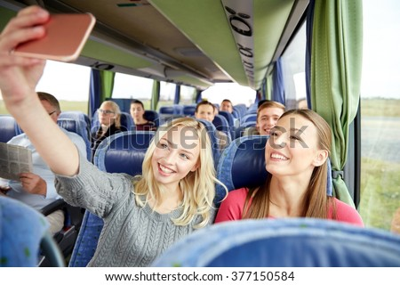 transport, tourism, road trip and people concept - happy young women or friends in travel bus taking selfie by smartphone