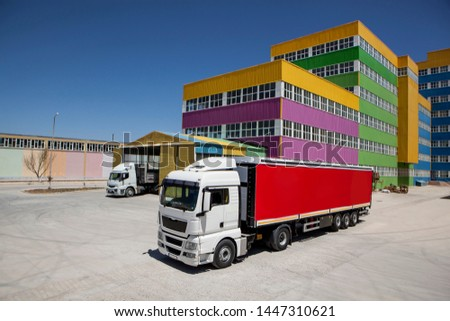 transport trucks with red containers in front of colorful buildings, under blue sky.  #1447310621