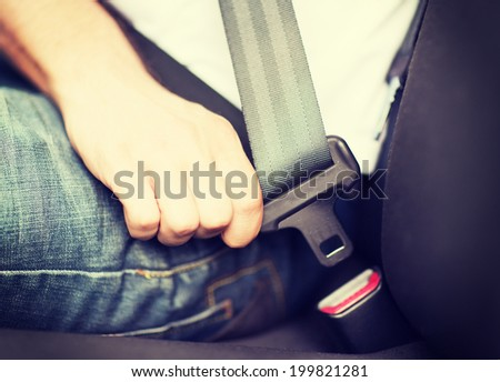 transportation and vehicle concept - man fastening seat belt in car Foto stock ©