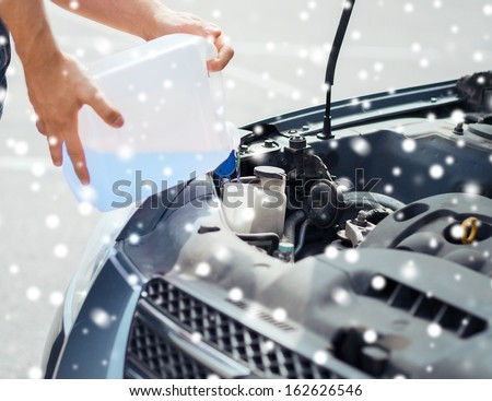 transportation and vehicle concept - man opening car bonnet and filling windscreen water tank with washing liquid