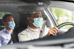 transportation, health and people concept - indian male taxi driver driving car with passenger wearing face protective medical mask for protection from virus disease