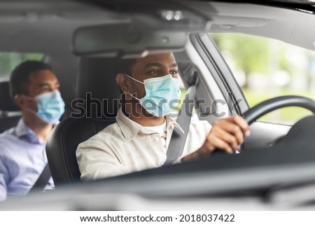transportation, health and people concept - indian male taxi driver driving car with passenger wearing face protective medical mask for protection from virus disease Stockfoto ©