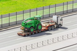 Transportation of agricultural machinery harvester on a trailer of a truck loading platform on a highway in the city