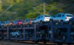 Transportation of cars by train. Autorack with cars. New cars transported with railway platforms. Panning effect. No logo or brand. SUV