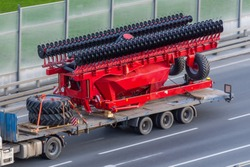 Transportation of large agro-complex machines for cultivating and sowing crops on long trailers by trucks along the highway in the city