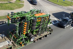 Transportation of new agricultural machinery by truck on a city street, on a highway, ring road.