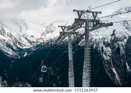 Transportation of tourists in a winter ski resort. Metal poles in the form of poles. Beautiful view of the snowy mountains and cable car in winter.