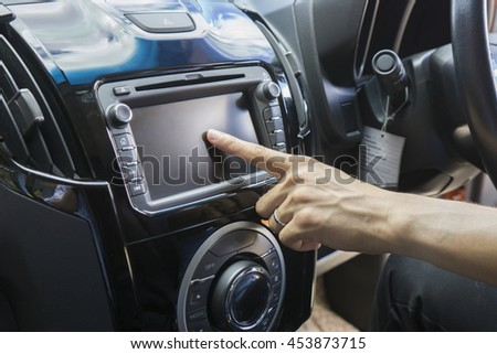 Transportation,technology and vehicle concept - man using car system control pushing panel button screen interface modern design