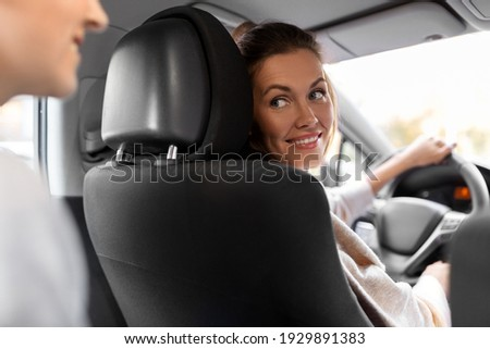 transportation, vehicle and people concept - happy smiling female driver driving car with passenger Foto stock ©