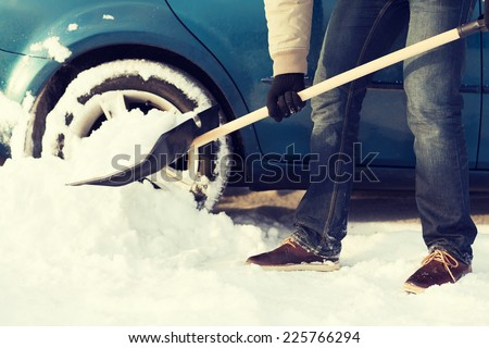 transportation, winter and vehicle concept - closeup of man digging up stuck in snow car #225766294