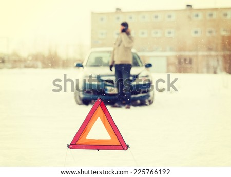 transportation, winter and vehicle concept - closeup of man with broken car, warning triangle and smartphone