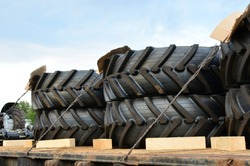 Transporting logistics a large wheels for agriculture tractors on platform of the freight train by rail. The protector of a large rubber wheel. Import/export of the tyre, tire and farming equipment.