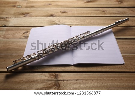 transverse flute and music score rest on a wooden board #1231566877