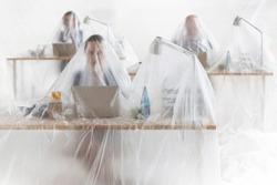 Trapped business colleagues using laptops at desks covered in plastic, creative conceptual photo showing that people become trapped in their jobs and careers that takes up all their time