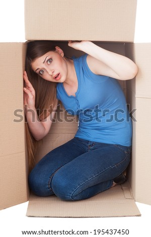Trapped inside. Shocked young woman looking at camera while sitting in a cardboard box