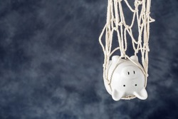 Trapped piggy bank in net on dark background with copy space. Avoid debt traps and speculation. Savings and retirement financial scams