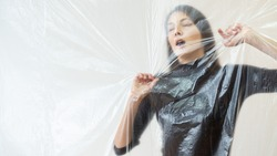 Trapped woman. Defocused portrait. Social isolation. Depression helpless. Claustrophobia disease. Helpless lady gaspingly touching transparent plastic film isolated neutral copy space.