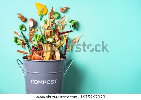 Trash bin for composting with leftover from kitchen on blue background. Top view. Recycling scarps concept. Sustainable and zero waste lifestyle Foto d'archivio ©