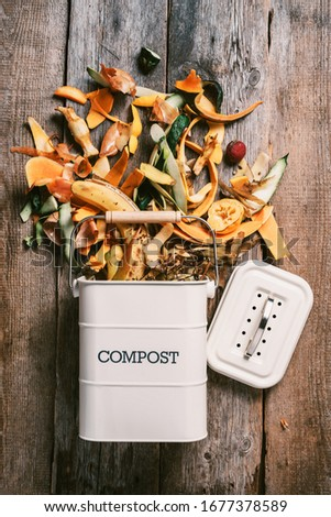 Trash bin for composting with leftover from kitchen on wooden background. Top view. Recycling scarps concept. Sustainable and zero waste lifestyle Foto d'archivio ©