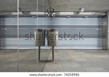 Trash can and closed store front shutters along a mirror wall in a deserted subway station
