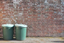 trash can dustbin rubbish bin garbage trashcan can outside against brick wall trash background with copy space - stock photo, stock photograph, image picture