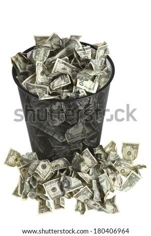 Trash can full of dollar bills